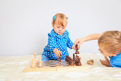 Little daughter playing chess with brother Royalty Free Stock Image