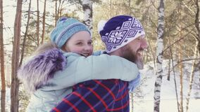 A little daughter riding a bearded father strolling through the woods and smiling. A little daughter riding a bearded father strolling through the forest and stock video