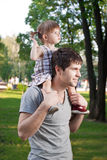 Little daughter riding father. On shoulders stock photography