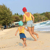 Little daughter running with mother on the beach Royalty Free Stock Photos