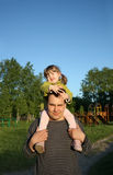 Little daughter sits on shoulders of father and keeps Stock Image