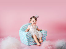 Little daughter sitting on an infantine armchair Stock Images