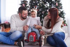 Little daughter sitting on retro toy car with parents near Chris. Closeup of little daughter sitting on retro toy car with parents near Christmas tree royalty free stock images