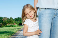 Little daughter standing near her mommy Royalty Free Stock Images