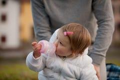 Little daughter sucking from her feeding bottle Stock Photo