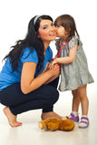 Little daughter tells secret to mother. Little daughter telling a secret or kissing mother in their home stock photo