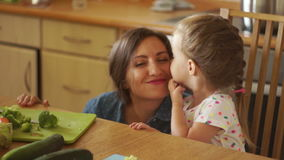 The little daughter thanks her mother for dinner. She kisses and strokes her face with her hand. Thanks. Education of stock footage