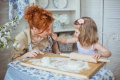 Little daughter touches a nose of her mother on a kitchen. A little daughter touches a nose of her mother on a kitchen Royalty Free Stock Photos