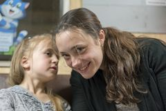 Little daughter is whispering something to her mother. royalty free stock image