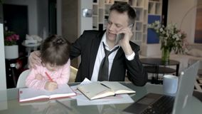 Daughter helping father working at home stock video