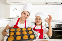 Little daughter and young mother presenting and showing tray with muffins Royalty Free Stock Images