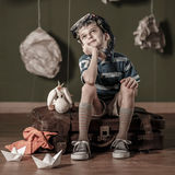 Little daydreamer sitting on suitcase Stock Images