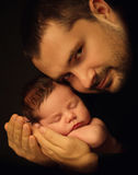 Little 15 days old baby lying securely on his Dad`s arms, against a black background Royalty Free Stock Photography
