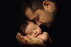 Little 15 days old baby lying securely on his Dad`s arms, against a black background Stock Photo