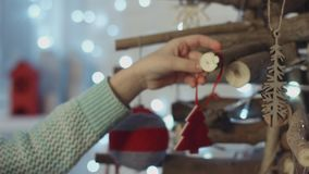 Little decorating wooden Christmas tree with toys. Little decorating wooden Christmas tree with fleece figure of the tree stock video footage