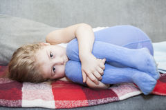 Little defenseless child huddled on the couch Stock Photography