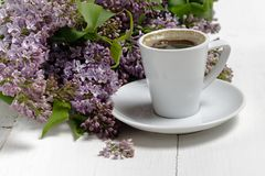 Little delicate elegant bouquet of spring flowers and a teacup on white wooden table, morning breakfast royalty free stock photo