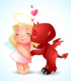 Little Demon's Kiss. Little demon boy is kissing a smiling angel girl Royalty Free Stock Photo