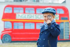 Little detective. Funny boy looking through magnifying glass near english schoolbus Stock Photography