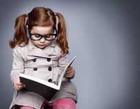 Little detective. Little smart girl holding a book and reading it while sitting on a stool Stock Photo