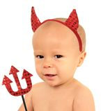 Little devil. One year old baby boy of Caucasian and Asian heritage wearing devil horns Royalty Free Stock Images