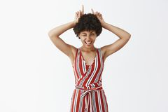 Little devil lives inside of me. Portrait of flirty and joyful good-looking carefree african american woman in stylish. Striped overalls winking playfully and royalty free stock photos