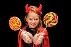 Little devil with lollipops. Kid in halloween costume of devil with lollipops, isolated on black stock photo