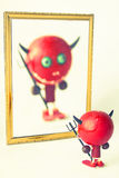 Little devil. Toy  in the mirror Royalty Free Stock Photo