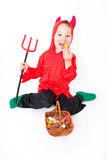 Little devil. With trident eating sweets stock photography