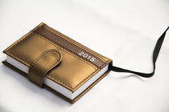 Little diary for year 2015. Closeup of a little diary photographed indoors, on a white sheet. It is brown-gold color, very small-around 10cm long and 4 cm wide royalty free stock images