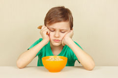 Little discontented boy does not want to eat porridge. Little discontented boy does not want to eat a porridge stock photography