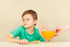 Little discontented boy refuses to eat porridge Stock Photo