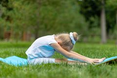 A little disgruntle blue-eyed, curly blonde girl in a white gymnastic suit is doing stretching