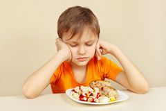 Little displeased boy does not want to eat pasta with rissole Stock Photography