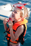 Little diver. Smiling little girl in life jacket and diving mask and snorkel on sea water background Royalty Free Stock Image
