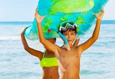 Little divers holding swimming mattress overhead. Portrait of little boy in scuba mask and girl in bikini carrying big swimming mattress overhead at the seaside stock photo