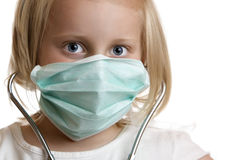 The little doctor. Little child plays doctor with stethoscope and mask Stock Photo