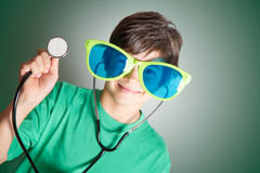 Little doctor. Child with glasses and stethoscope in hand Stock Photo
