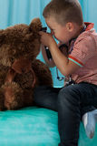 Little doctor examining teddy bear Stock Photography