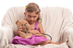 Little doctor girl with stethoscope and toy Stock Photos