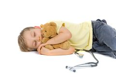 Little Doctor And Patient. Little boy sleeping with his stuffed animal patient in his arms.  A stethoscope is on the floor beside him.  Isolated on white.  Taken Stock Photography