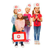 Little doctors giving an emergency aid. Portrait of four little doctors with red toy  first aid box, isolated on white Royalty Free Stock Images