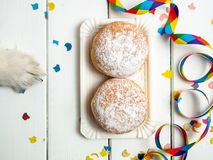Little dog paw and donut donuts with carnival decoration on a white background royalty free stock photo