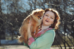 Little dog and pretty red haired woman playing outdoor Stock Photography