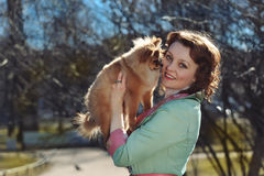 Little dog and pretty red haired woman playing outdoor Stock Images