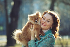 Little dog and pretty red haired woman playing outdoor Royalty Free Stock Photography