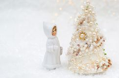 A little doll in winter clothes is looking at the New Year tree. Christmas tree with pearls and beads beautiful bokeh background. A little doll in winter stock image