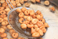Little donuts in hot oil. Strainers hot oil through a sieve Royalty Free Stock Image