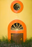 The little door and round window in a yellow wall Royalty Free Stock Photos