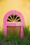 The little door in a yellow wall and green grass Royalty Free Stock Photo